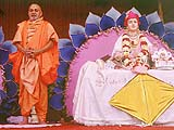 Pramukh Swami on stage, begging for alms for the social and religious activities of the sanstha