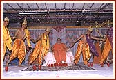 Swamishri holding hands with kishores during a folk dance