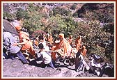 Swamishri being carried through narrow, steep pathways towards the caves