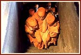 Swamishri being carried on a flight of stairs to a Buddhist cave