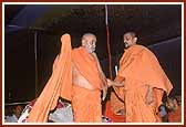 Swamishri, gripped by a sudden cold shiver, ties his upper garment during an evening assembly