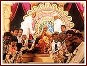 The leading devotees of Valsad and Tithal offer a giant garland to Swamishri