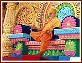 Swamishri seated on a resplendent stage, serenely chanting the holy name of Swaminarayan