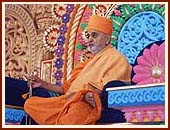Swamishri seated on a colorful giant stage, serenely chanting the holy name of Swaminarayan