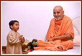 At 10.30 pm, before retiring to bed Swamishri patiently blesses a child, listens to him and pleases him with a handful of chocolates. Even after a hectic day of activities Swamishri responds with joy, freshness and humor at the child's casual and innocent talk.