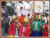 Saints pull a float with Lord Swaminarayan's murti, while children dance in front
