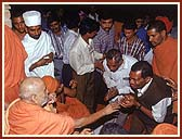Swamishri giving a rosary in appreciation to each Tandel volunteer