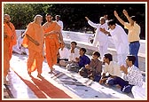 Swamishri responds to a jubiliant welcome by a few devotees while circumambulating the Smruti Mandir