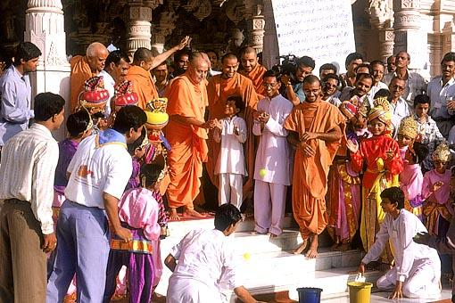At the request of volunteers Swamishri throws a ball in a bucket at the outset of Children's Day