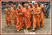 Despite the soggy ground Swamishri walks on to see the construction work