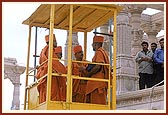 Being elevated to the mandir floor in a cabin by the construction crane