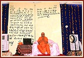 Swamishri after completing his morning puja. Backdrop of a magnified page of diary in Swamishri's on words about the day of his appontment as president, Pramukh Varni Celebration (English date), 21 May 2000