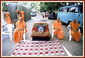 Swamishri sits on an ordinary chair with Thakorji placed on a decorated sofa on the road outside his residence