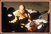 ... During which Swamishri is engrossed in reading letters in the dim light