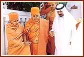 The Sheikh holds Swamishri's hand and sees him to the palace gate