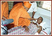 Swamishri is apprised of Shrujan Singh's condition, the NSG commando injured during Operation Thundernight, by the doctors and blesses him and prays for his recovery. Swamishri gently blesses him with the touch of his hand and showers sacred rose petals