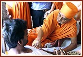 Swamishri holds Harikrishna Maharaj before each of the injured, blesses them by gently placing his hand on them and encourages them with words for their quick recovery