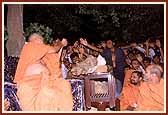 Swamishri sprinkling the consecrated color on the excited youths and sadhus