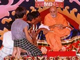 Swamishri encouraging tribal children, Atladra