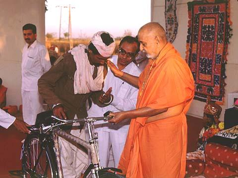 Swamishri offering a bicycle to a cured leper, Jamnagar