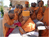 Sadhus welcome Swamishri with a garland