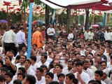 In spite of rain, devotees remain seated in Swamishri's puja darshan