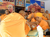 Kothari Swami welcomes Swamishri with a garland