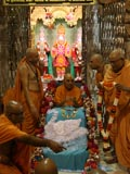 Sadhus honor Swamishri with a shawl and a garland of rakhis