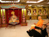 Swamishri engaged in darshan Thakorji in a hiindolo