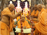 Senior sadhus honor Swamishri with a garland on the occasion of his 1,111th Purnima
