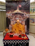 Murti of Brahmaswarup Yogiji Maharaj with his puja arranged for darshan with a backdrop of Akshar Deri