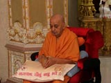 Swamishri reverentially picks up the Shikshapatri from Yogiji Maharaj's puja and reads from it