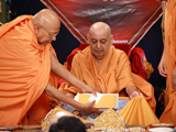 Pujya Tyagvallabh Swami with symbolic offerings from the devotees