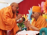 Pujya Ishwarcharan Swami performs chandan archa on the forehead of Swamishri