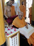 Swamishri reverentially touches the charanarvind in Rang Mandap