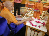 Swamishri reverentially touches holy charnarvind of Bhagwan Swaminarayan in the Rang Mandap