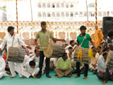 Tribal devotees play drums before Swamishri