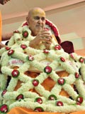 Swamishri is honored with a shawl of flowers by senior sadhus