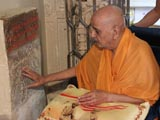 Swamishri reverentially touches sacred stone sanctified by Aksharbrahman Gunatitanand Swami