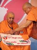 Pujya Ishwarcharan Swami gives an  Adhiveshan ID card to Swamishri