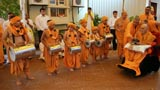 Swamishri is welcomed by children dressed as sadhus and playing dhols