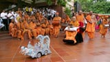 Swamishri drives the remote-controlled chariot of Harikrishna Maharaj accompanied by children