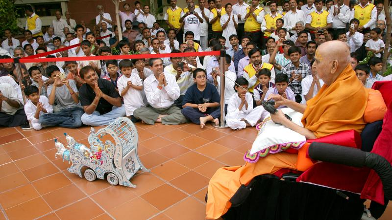 Devotees doing darshan of Swamishri driving the remote-controlled chariot of Shri Harikrishna Maharaj