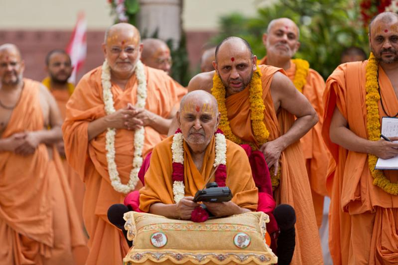 Swamishri drives the remote-controlled chariot of Harikrishna Maharaj in the mandir pradakshina
