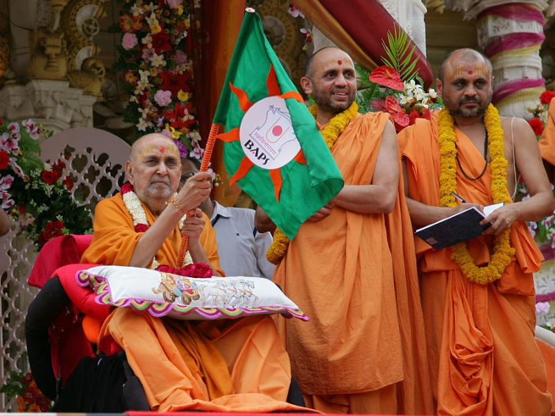 Swamishri waves a flag for the rathyatra to begin