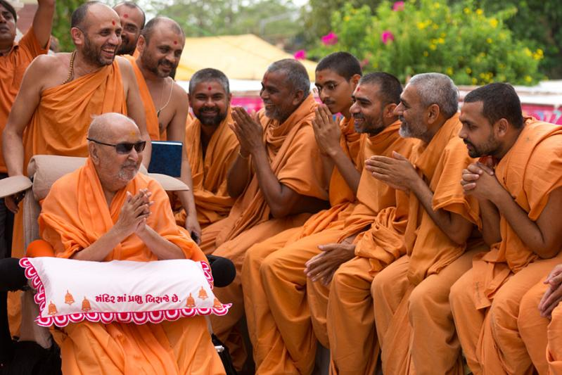 Swamishri in a divine, jovial mood with sadhus