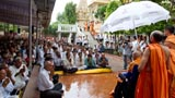A brief rain shower does not dampen the enthusiasm of devotees for Swamishri's darshan