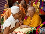 Swamishri initiates a youth, giving him parshadi diksha