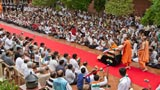Devotees welcome Swamishri while waving the Indian tricolor