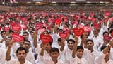 Youths in the audience wave heart-shaped cards
